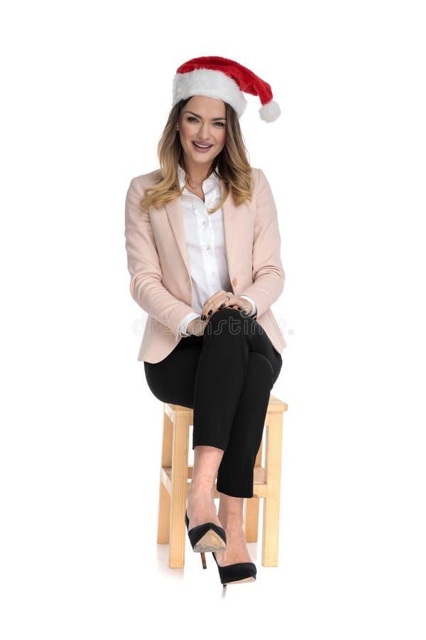 Die intelligente zufällige Frau, die Sankt-Kappe trägt, sitzt mit den gekreuzten Beinen lizenzfreies stockfoto