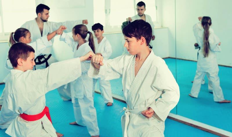 Die Jugendlichen, die neues Karate üben, zieht in Paare in der Klasse um stockbilder