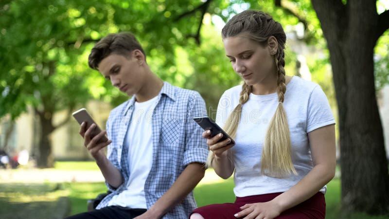Die Jugendlichen, die Telefon verwenden, anstatt, Mangel aufeinander einzuwirken an Kommunikation, gew?hnten stockfotos