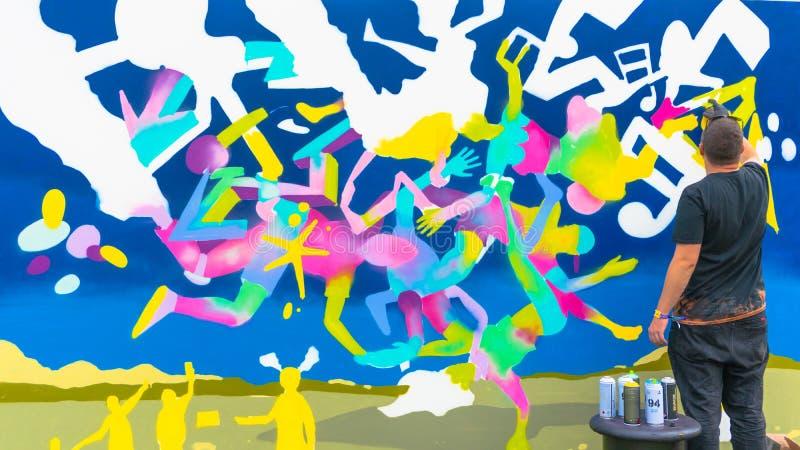 Die Jugendlichzeichnung mit Sprays - Graffitikünstlermalerei mit Aerosolfarbdosen auf der Wand stockfoto