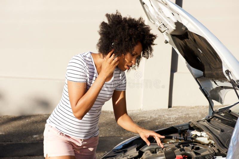 Die junge afrikanische Frau, die aufgegliedertes Auto bereitsteht, parkte auf der Straße und dem Fordern Unterstützung stockfotos