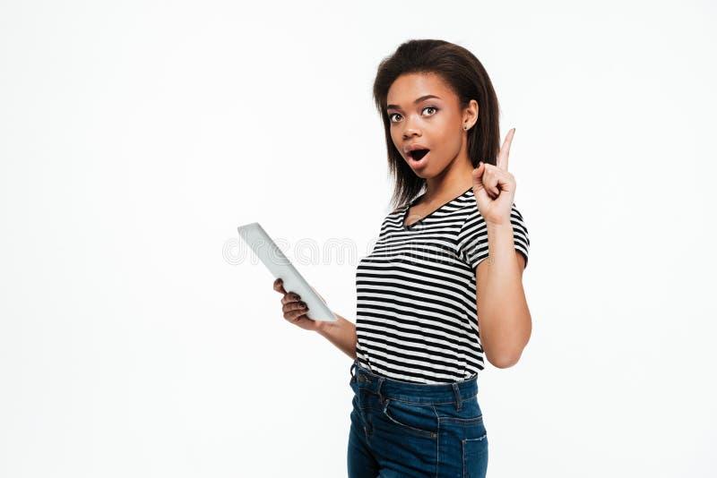 Die junge afrikanische Frau, die Tablet-Computer verwendet und haben eine Idee lizenzfreies stockfoto