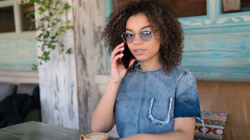 Die junge Afrofrau, die Kaffeepause-Innencafé isst, spricht sie mit ihrem Freund durch das Telefon lizenzfreie stockbilder