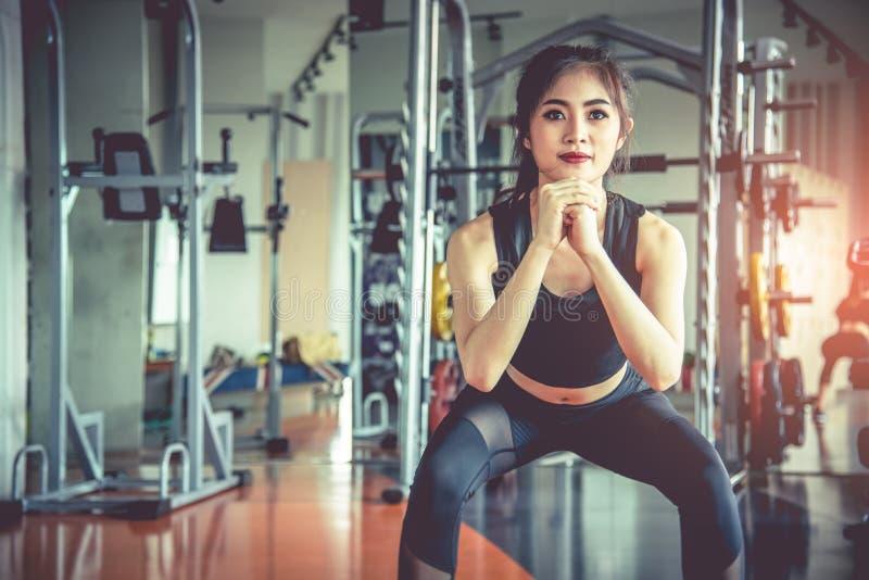 Die junge Asiatin, die untersetztes Training f?r Fett Burning und Di?t in der Eignung tut, tr?gt Turnhalle mit Sportausr?stung im stockfotos