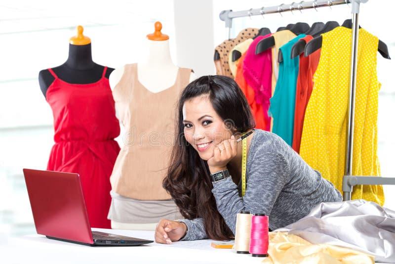 Die junge asiatische Designerfrau, die einen Laptop, lächelnd verwendet, kleidet hane lizenzfreie stockbilder