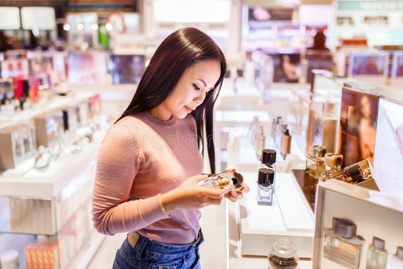 Die junge asiatische zutreffende Frau und beschließen, Parfüm im zollfreien Speicher am internationalen Flughafen zu kaufen lizenzfreie stockfotografie