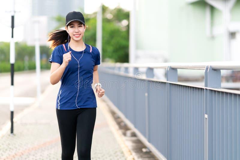 Die junge attraktive asiatische L?uferfrau, die in st?dtische Stadtstra?en- oder Fu?wegweise l?uft, h?ren Musik, die blaues oder  lizenzfreies stockbild