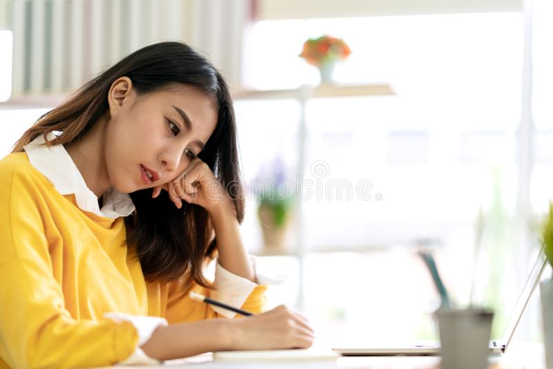 Die junge attraktive asiatische Studentin, die bei Tisch das Denken und das Schreiben der Zeitschrift merken sitzt eigenhändig, I lizenzfreie stockfotografie