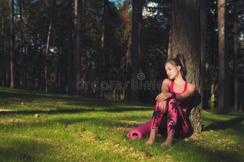 Die junge attraktive athletische Frau, die intelligente Uhr trägt, genießt letzte Strahlen der Sonne für den Tag nach ihrem Train stockbilder