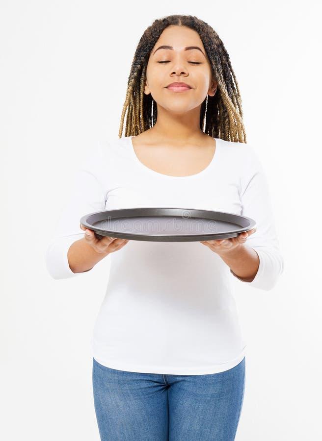 Die junge attraktive Frau, die leeren Pizzabehälter hält und schnüffeln die gute Geruchnahrung, die auf weißem Hintergrund lokali stockfoto