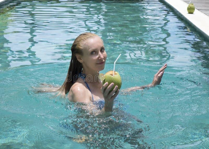 Die junge attraktive Frau mit dem langen Haar in einer Badebekleidung im Pool mit Cocktail in der Kokosnuss stockfoto