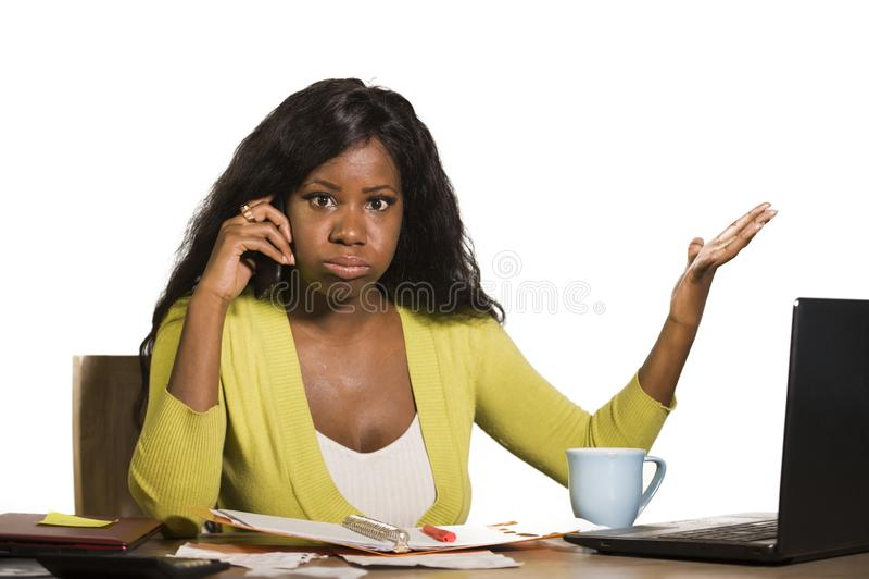 Die junge attraktive und beschäftigte schwarze afroe-amerikanisch Geschäftsfrau, die zu Hause den Bürocomputertisch spricht am be lizenzfreie stockfotografie