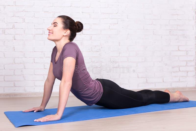 Die junge dünne Frau, die das Ausdehnen tut, trainiert über dem weißen wal Ziegelstein stockbild