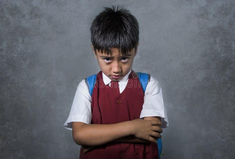 Die Junge, die eingeschüchtert wurden, missbrauchten Schüler in einheitlichem tragendem traurigem deprimiertem der Schultasche au stockbild