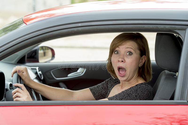 Die junge erschrockene Schönheit des weiblichen Fahrers des Anfängers neuen und betonte beim Fahren des Autos in der Furcht und i lizenzfreies stockfoto