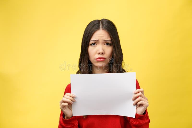 Die junge erwachsene Frau, die Blatt des leeren Papiers über lokalisiertem Hintergrund hält, betonte, entsetzt mit Schand- und Üb stockfotografie
