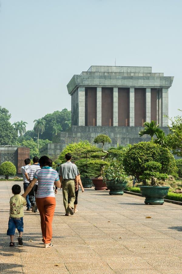 Die junge Familie, die in Richtung zu Ho Chi Minh-Mausoleum in Hanoi geht, konkurrieren stockfoto