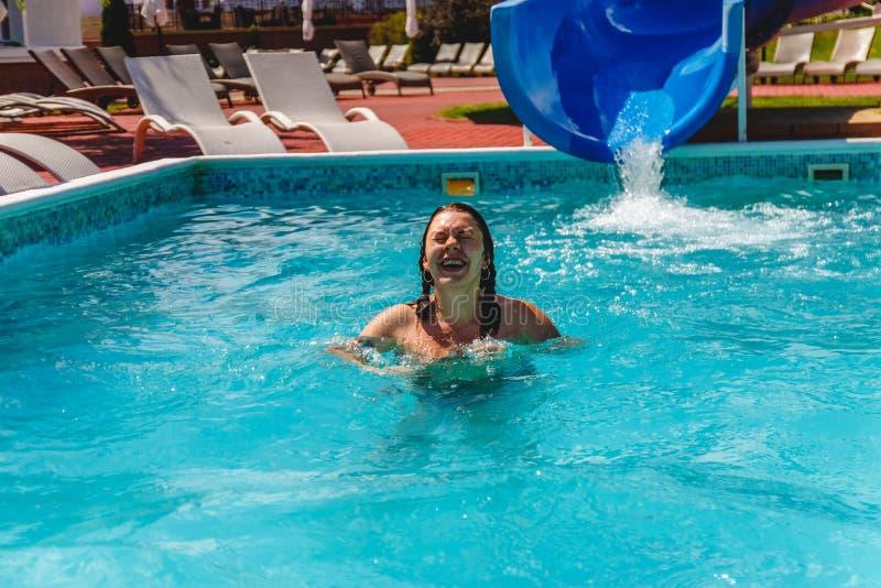 die junge Frau abgerutscht dem Waterslide in das Pool und in das Lachen lizenzfreie stockbilder