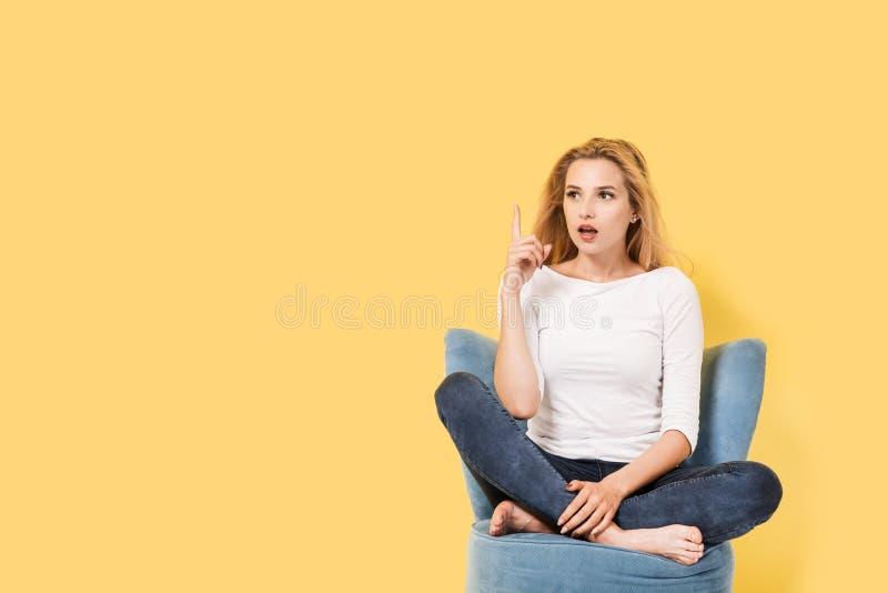 Die junge Frau, die auf einem Stuhl sitzt, erhielt eine Idee lizenzfreie stockfotografie