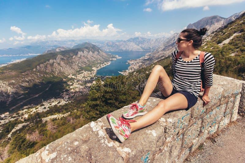 Die junge Frau, die Berg schauen und das blaue Meer gestalten Horizont landschaftlich stockfotos