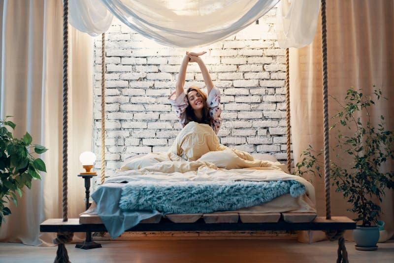 Die junge Frau, die in Bett nach ausdehnt, wachen in ihrer modernen Wohnung auf lizenzfreie stockfotografie