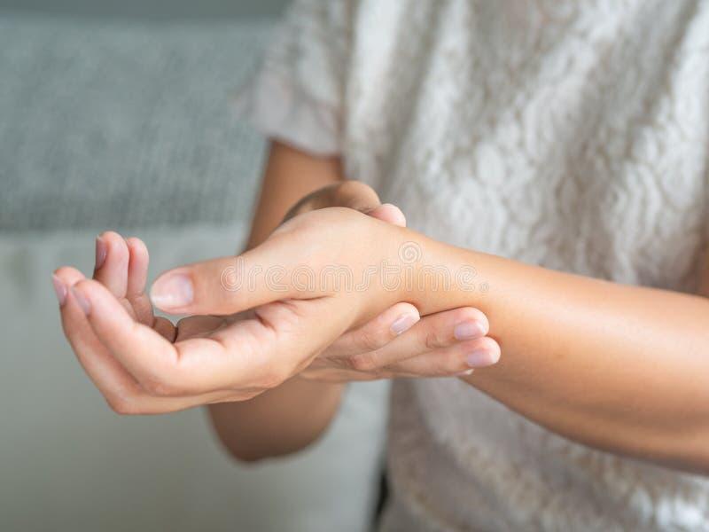 Die junge Frau der Nahaufnahme, die auf Sofa sitzt, hält ihre Handgelenkhandverletzung stockfoto