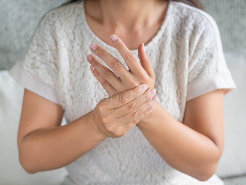 Die junge Frau der Nahaufnahme, die auf Sofa sitzt, hält ihre Handgelenkhandverletzung lizenzfreie stockbilder
