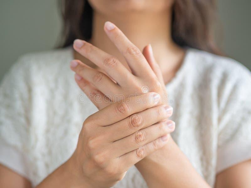 Die junge Frau der Nahaufnahme, die auf Sofa sitzt, hält ihre Handgelenkhandverletzung stockbild