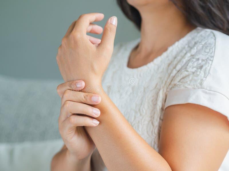 Die junge Frau der Nahaufnahme, die auf Sofa sitzt, hält ihre Handgelenkhandverletzung stockbilder