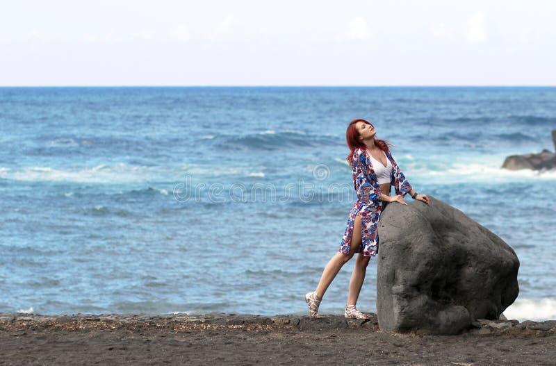 Die junge Frau der Rothaarigen, die in dem Meer steht lizenzfreie stockbilder