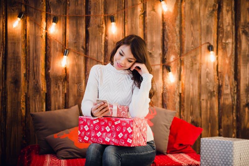 Die junge Frau, die auf einem Boden unter Verwendung der Handymitteilung nahe sitzt, verzierte Weihnachtswand mit Glühlampen stockfotos