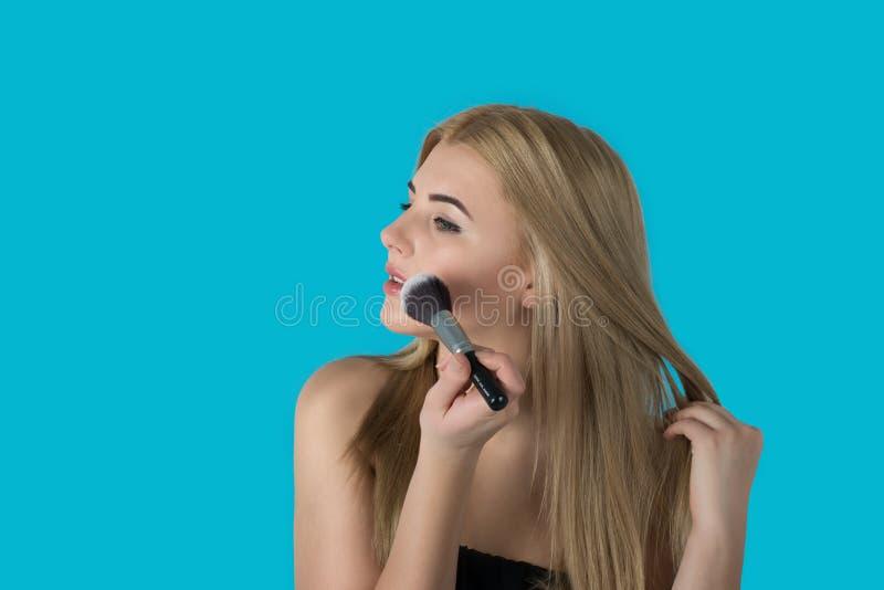 Die junge Frau die Blondine mit brushe für ein Make-up stockbilder
