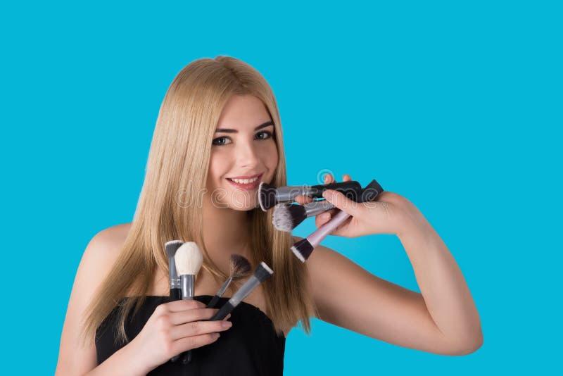 Die junge Frau die Blondine mit verschiedenen Bürsten für ein Make-up stockfotos