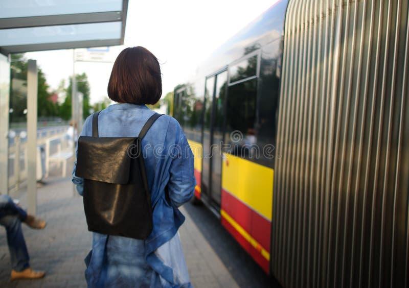Die junge Frau, die der Brunette auf der Bushaltestelle steht lizenzfreies stockfoto