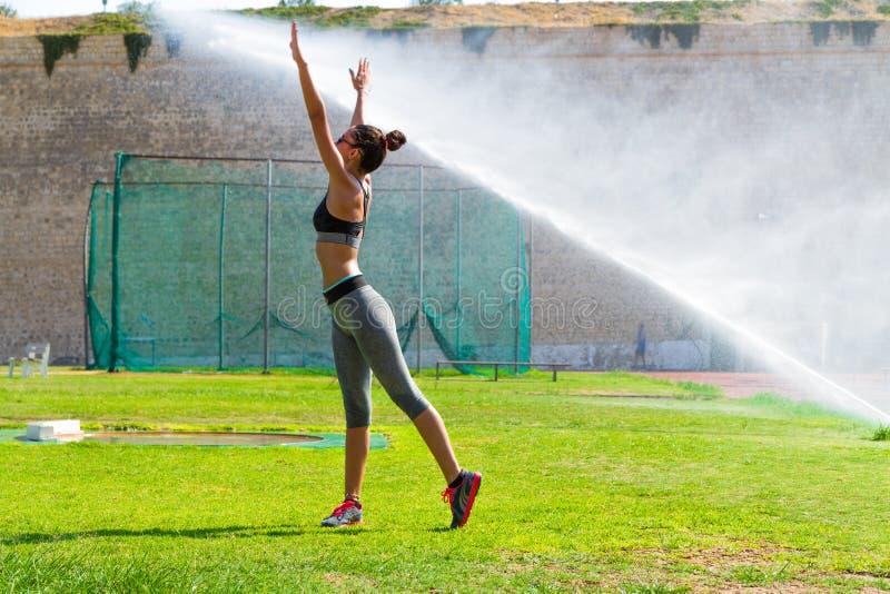 Die junge Frau, die Eignungstraining in der lokalen Öffentlichkeit tut, trägt Stadion draußen zur Schau stockfoto
