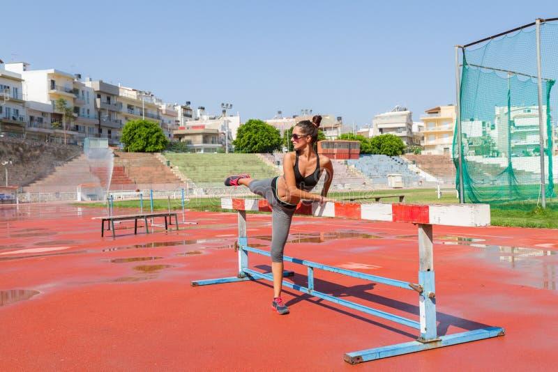 Die junge Frau, die Eignungstraining im Einheimischen tut, trägt Stadion im Freien zur Schau stockbild