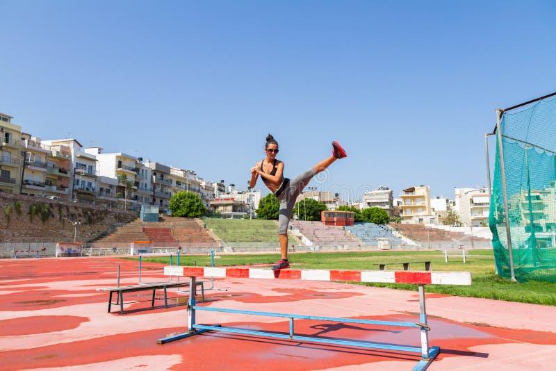 Die junge Frau, die Eignungstraining im Einheimischsportstadion tut, übertreffen stockfoto