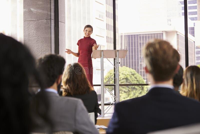 Die junge Frau, die Geschäftsseminar darstellt, gestikuliert zum Publikum stockfotos