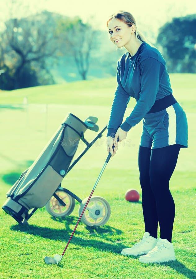 Die junge Frau, die Golf spielt, wird Ball schlagen lizenzfreie stockfotografie