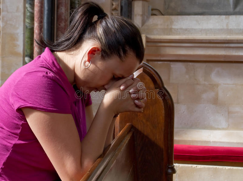 Die junge Frau, die innen verloren ist, beten stockfotografie