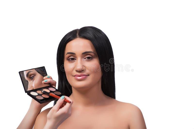 Die junge Frau, die Make-up lokalisiert auf Weiß erhält lizenzfreie stockfotografie