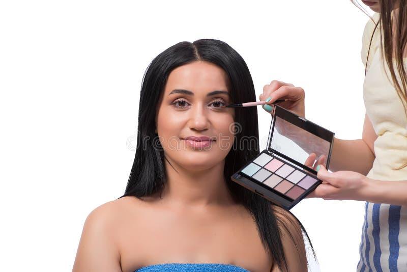 Die junge Frau, die Make-up lokalisiert auf Weiß erhält stockfoto