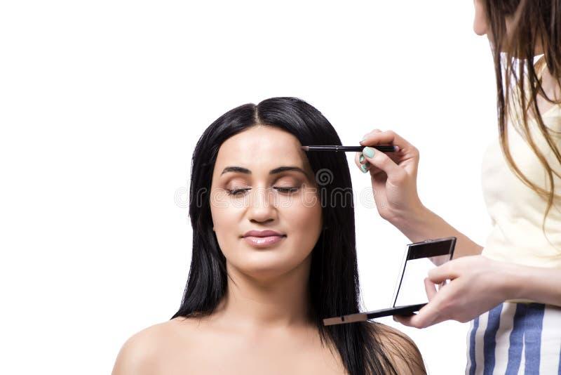 Die junge Frau, die Make-up lokalisiert auf Weiß erhält stockfotos