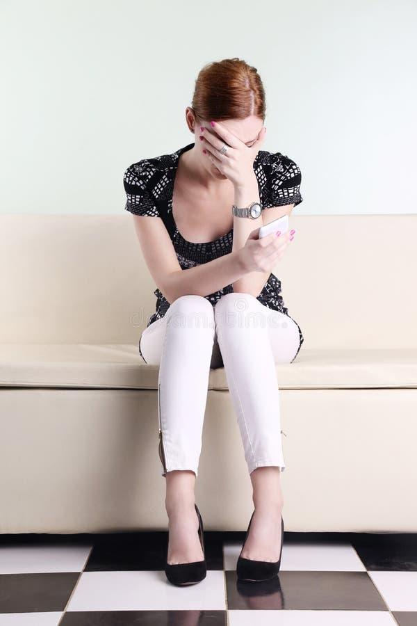 Die junge Frau, die mit sitzt, überreichen ihr Gesicht lizenzfreie stockbilder