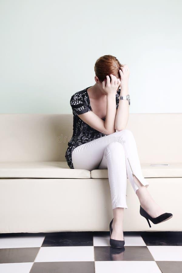 Die junge Frau, die mit sitzt, überreicht ihr Gesicht stockbilder