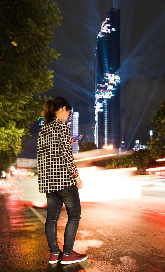 Die junge Frau, die steht, spielend intelligentes Telefon in der Nachtzeit, haben Maha lizenzfreies stockbild