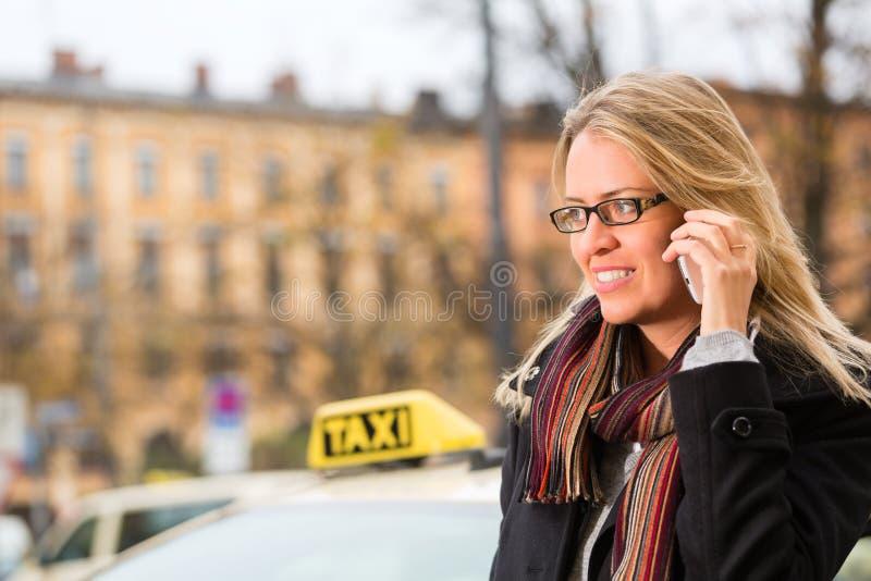 Junge Frau vor Taxi mit Telefon stockbild