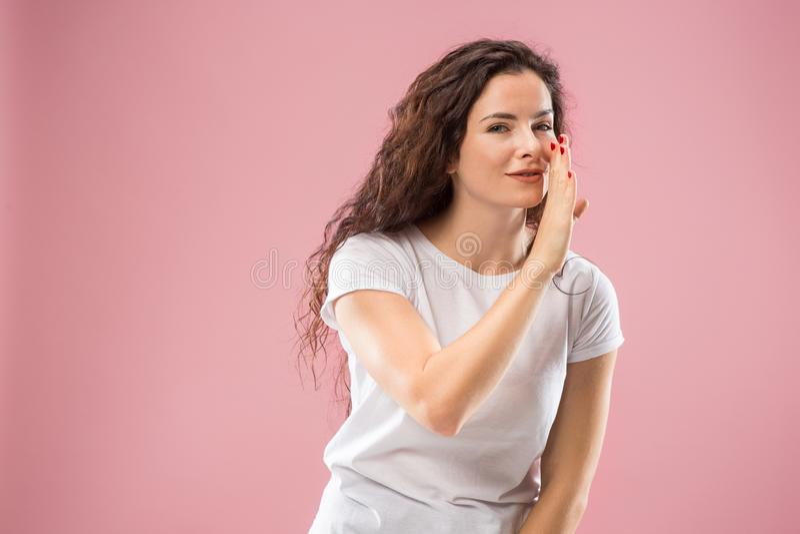 Die junge Frau, die ein Geheimnis hinter ihr flüstert, überreichen rosa Hintergrund lizenzfreies stockfoto