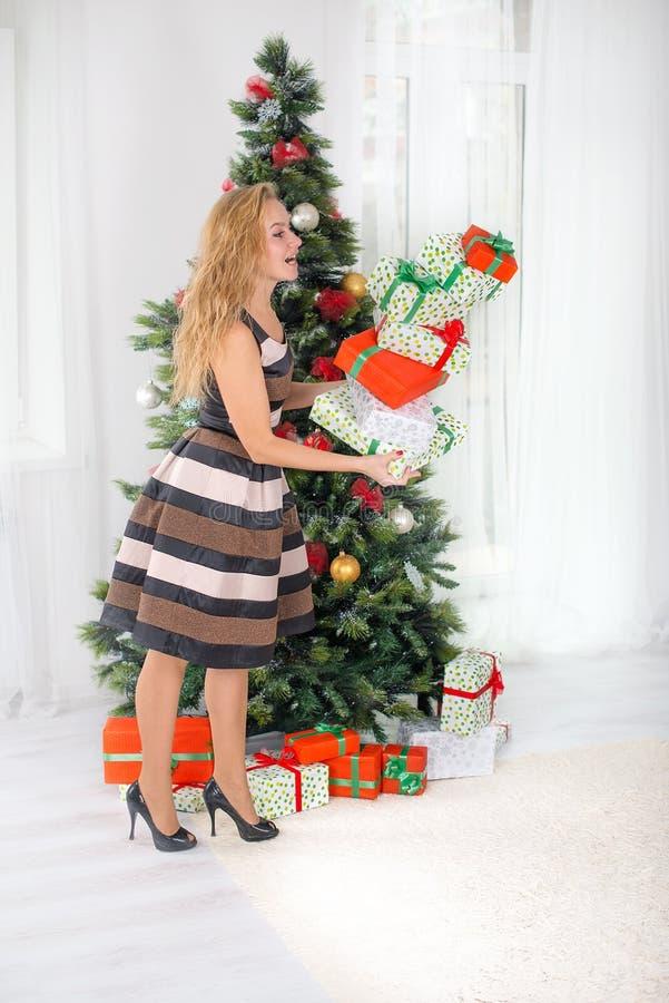 Die junge Frau hält viele Weihnachtsgeschenke in der Hand lizenzfreie stockfotos