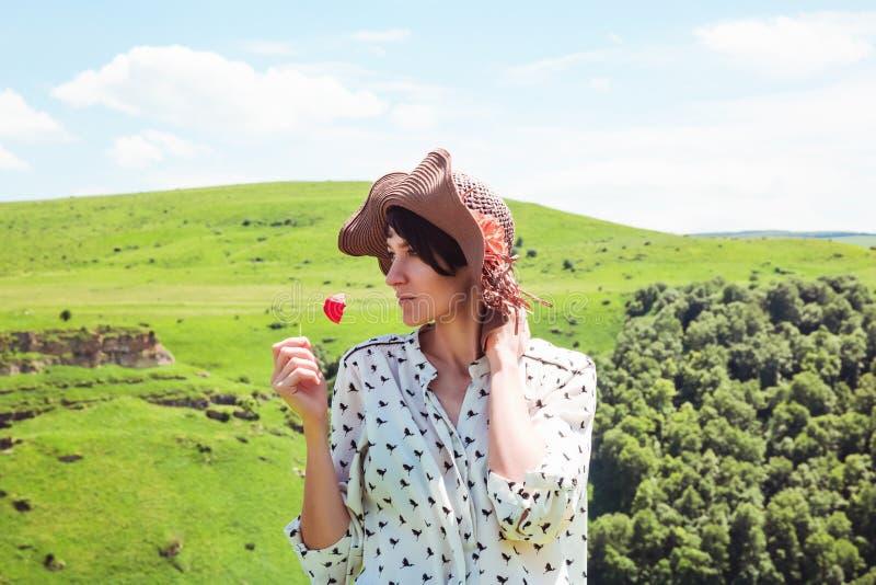 Die junge Frau im Hut Berge genießend gestalten aktives des roten Gefühlkonzept-Abenteuers des Blume Reise-Lebensstils glückliche stockfotografie